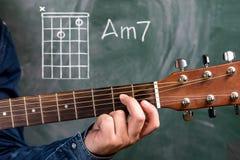 Obsługuje bawić się gitara akordy wystawiających na blackboard, akord Am7 obrazy royalty free