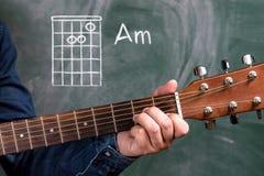 Obsługuje bawić się gitara akordy wystawiających na blackboard, akord Am obraz stock
