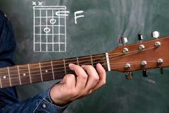 Obsługuje bawić się gitara akordy wystawiających na blackboard, akord F zdjęcie royalty free