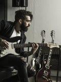 Obsługuje bawić się jego gitarę elektryczną w muzycznym studiu zdjęcie stock