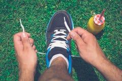Obsługuje biegacza wiąże obuwiane koronki na trawie i szklanej butelce świeży o Zdjęcia Stock