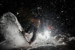 Obsługuje breathtakingly jechać snowboard w zmroku pod śniegiem Obraz Royalty Free