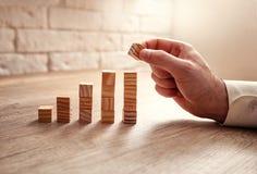 Obsługuje budować narastającego pieniężnego wykres używać drewnianych bloki obrazy royalty free