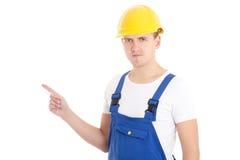 Obsługuje budowniczego wskazuje na coś iso w błękita mundurze i hełma Zdjęcia Royalty Free