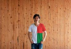 Obsługuje być ubranym Madagascar flagi koloru koszula i pozycja z dwa rękami wewnątrz dyszy kieszenie na drewnianym ściennym tle obraz royalty free