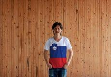 Obsługuje być ubranym Slovenia flagi koloru koszula i pozycja z dwa rękami wewnątrz dyszy kieszenie na drewnianym ściennym tle obraz royalty free