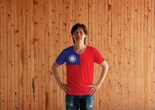 Obsługuje być ubranym Tajwan flagi koloru pozycję z akimbo na drewnianym ściennym tle i koszula zdjęcia royalty free