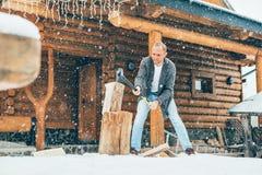 Obsługuje ciapania drewno na śnieżnym jardzie dla domowej graby z ciężkim płatek śniegu tłem Zimy wsi wakacji pojęcia wizerunek zdjęcia stock
