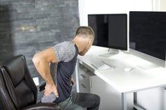Obsługuje cierpienie od backache podczas gdy siedzący przy komputerowym biurkiem w biurze obraz royalty free