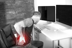 Obsługuje cierpienie od backache podczas gdy siedzący przy komputerowym biurkiem w biurze zdjęcie stock