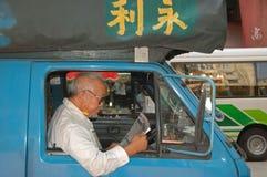 Obsługuje czytać gazetę przy jego ciężarówką w Hongkong Obraz Royalty Free