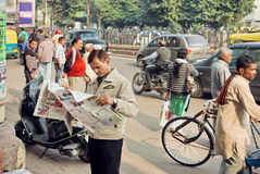 Obsługuje czytać gazetę w tłumu ruchliwie ludzie na ulicie Zdjęcie Stock