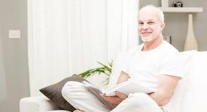 Obsługuje czytać książkę w jego żywym pokoju Obrazy Royalty Free