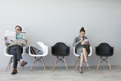 Obsługuje czytelniczą gazetę i kobiety używa cyfrową pastylkę Zdjęcia Stock
