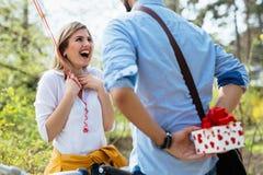Obsługuje dawać niespodzianka prezentowi jego urocza dziewczyna jak teraźniejszość obrazy royalty free