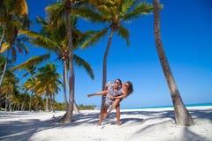 Obsługuje dawać piggyback przejażdżce dziewczyna przy Karaibską plażą zdjęcia stock