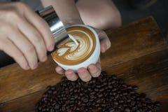 Obsługuje dolewanie śmietankę w kawę Fotografia Royalty Free