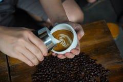 Obsługuje dolewanie śmietankę w kawę Zdjęcie Royalty Free