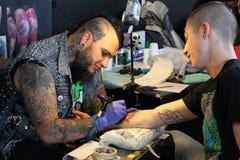 Obsługuje dostawać tatuaż, przy tatuażu studiiem Obrazy Stock