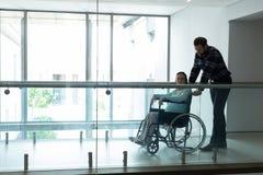 Obsługuje dosunięcie kobiety w ciąży na wózku inwalidzkim w korytarzu fotografia royalty free