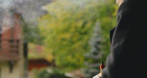 Obsługuje dymić vape papieros podczas gdy siedzący outside zbiory wideo