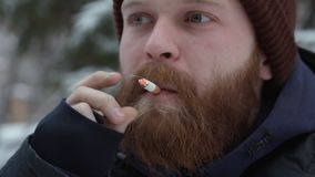 Obsługuje dymienie papieros, młodego brodatego modnisia w kapeluszu i kurtki, przy lasem na naturalnym tle zbiory wideo