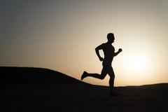 Obsługuje działającą sylwetkę przy zmierzchem, młody caucasian biegający w górze Obrazy Royalty Free