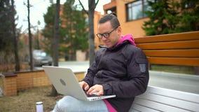 Obsługuje działanie na laptopie i uśmiechać się dolly strzał, outdoors, Latynoski mężczyzna jest ubranym szkła pracuje z laptopem zdjęcie wideo