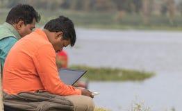 Obsługuje działanie na laptopie siedzi plenerowego, jeziornego widok, Kamalapur, Hospet, Karnataka, India na 22nd 2018 Październi zdjęcie royalty free