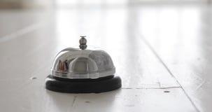 Obsługuje dzwonienie hotelowego recepcyjnego dzwon, męskiego ręki dosunięcia zakwaterowania wywoławczy dzwon na drewnianym recepc zbiory