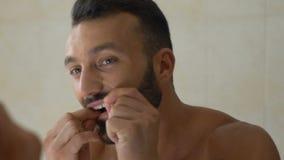 Obsługuje flossing jego zęby przed lustrem w łazience, stomatologiczna opieka, oralna higiena zbiory