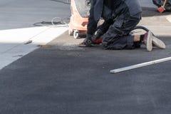 Obsługuje i koryguje wysokość asfalt na ulicie używać ostrzarza obraz royalty free