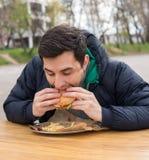 Obsługuje jeść bardzo smakowitego hamburger w ulicznej karmowej kawiarni Obrazy Royalty Free