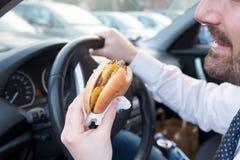 Obsługuje jeść hamburger podczas gdy jadący jego samochód Fotografia Royalty Free