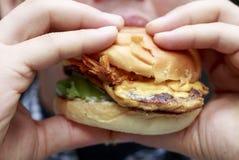 Obsługuje jeść hamburger, w górę, niezdrowy łasowania pojęcie zdjęcie stock