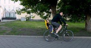 Obsługuje jeździeckiego bicykl z dzieckiem w zbawczym siedzeniu zbiory wideo