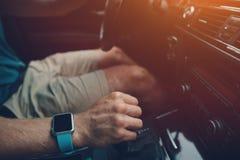 Obsługuje jechać samochód przy słonecznym dniem, mądrze zegarek na jego ręce, inside zdjęcie royalty free