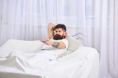 Obsługuje kłaść na łóżku, ogląda tv, białe zasłony na tle Facet na poważnej twarzy używać pilot do tv dla zmiany Obrazy Royalty Free