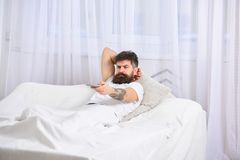 Obsługuje kłaść na łóżku, ogląda tv, białe zasłony na tle Facet na poważnej twarzy używać pilot do tv dla zmiany Fotografia Royalty Free