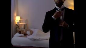 Obsługuje kładzenie garnitur dalej i opuszczać sypialnej kochanki w łóżku, cyganienie obraz royalty free