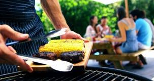 Obsługuje kładzenie piec na grillu kukurudzy na tacy dla słuzyć i mięso przy outdoors grilla przyjęciem zbiory