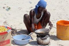 Obsługuje kucharstwo na plaży z prostą prowizoryczną kuchnią Obrazy Stock