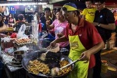 Obsługuje kulinarnego ryżowego tort przy PJ Pasar Malam obrazy stock