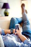 Obsługuje lying on the beach na kanapie używać smartphone i mądrze zegarek zdjęcia royalty free