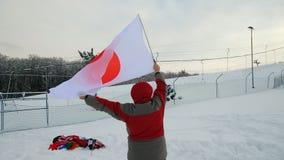 Obsługuje machać flaga Japonia w zimie na narciarskim skłonie zbiory