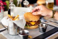Obsługuje mieć cheeseburger z dłoniakami w barze zdjęcia stock