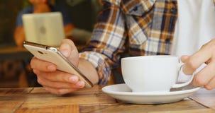 Obsługuje mieć kawę podczas gdy używać telefon komórkowego w kawiarni 4k zdjęcie wideo