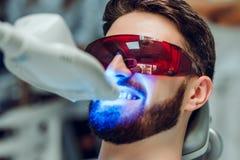 Obsługuje mieć zęby bieleje stomatologicznym ULTRAFIOLETOWYM dobieranie przyrządem, stomatologiczny asystent bierze opiekę pacjen zdjęcie stock