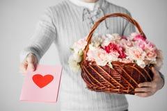 Obsługuje mienia koszykowy pełnego kwiaty i pocztówka zdjęcie stock