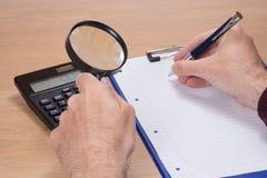 Obsługuje mienia powiększać i pisze w palcach - szkło zdjęcia stock